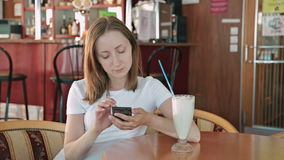 Woman using smartphone in cafe stock video footage