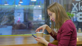 Woman using smartphone in cafe. Technology and fast food concept stock video