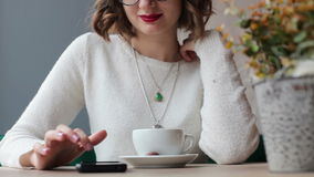 Woman using smartphone in a cafe. Young woman using smartphone in a cafe stock video footage
