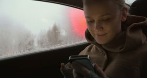 Woman using smartphone in the car stock video footage