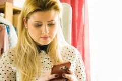 Woman using smartphone checking social media. Woman having neutral face expression using smartphone checking social media or writing message Stock Image