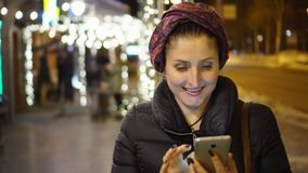 Woman using smartphone in the city. The woman in brisk night time of day watches something cheerful that lifted her insistance in the telfena. It can be a stock video footage