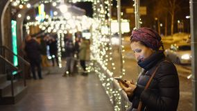 Woman using smartphone in the city. The woman in brisk night time of day watches something cheerful that lifted her insistance in the telfena. It can be a stock video