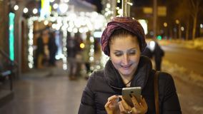 Woman using smartphone in the city. The woman in brisk night time of day watches something cheerful that lifted her insistance in the telfena. It can be a stock footage