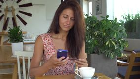Woman using smartphone with credit card for shopping online in cafe stock video footage