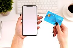 Woman using smartphone and credit card at work. White empty screen. Online shopping, food delivery stock photography