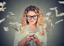 Woman using smartphone with dollar bills flying away from screen royalty free stock photos