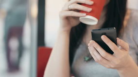 Woman using smartphone, drinking coffee in cafe. stock video footage