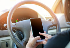 Woman using a smartphone while driving. Stock Image