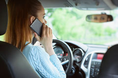 Woman using smartphone while driving a car stock image