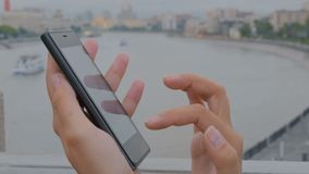 Woman using smartphone on embankment stock video