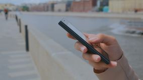 Woman using smartphone. On embankment - scrolling and touching stock footage