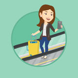Woman using smartphone on escalator in airport. Stock Photography