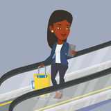 Woman using smartphone on escalator in airport. Stock Images