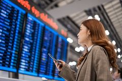 Woman using smartphone with flight information board at airport royalty free stock image