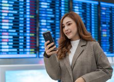 Woman using smartphone with flight information board at airport stock photo