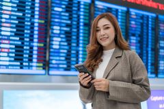 Woman using smartphone with flight information board at airport royalty free stock photo