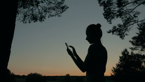 Woman using smartphone in forest after sunset stock video footage