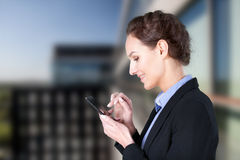 Woman using smartphone. In front of company building royalty free stock photo
