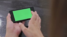 Woman using smartphone with green screen. Close up shot of woman`s hands with mobile. Various hand gestures - scrolling and touching stock footage