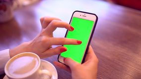 Woman using smartphone with green screen. Close-up video of woman`s hands scrolling pages on mobile phone. Chroma key. Woman using smartphone with green screen stock footage