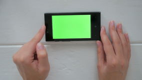 Woman using smartphone with green screen. Woman using horizontal smartphone with green screen. Close up shot of woman`s hands with mobile Close up shot of woman` stock footage