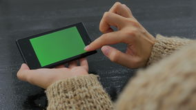 Woman using smartphone with green screen. Woman using horizontal smartphone with green screen. Close up shot of woman`s hands with mobile Close up shot of woman` stock video footage