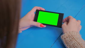 Woman using smartphone with green screen. Woman using horizontal smartphone with green screen. Close up shot of woman`s hands with mobile. Technology, chroma and stock footage