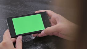 Woman using smartphone with green screen. And scrolling. Close up shot of woman`s hands with mobile stock video footage