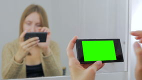 Woman using smartphone with green screen stock video footage