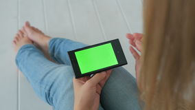 Woman using smartphone with green screen. Woman sitting on the white wooden floor and using horizontal smartphone with green screen. Close up shot of woman`s stock video