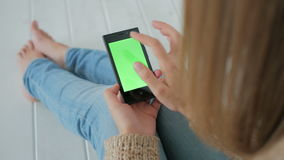 Woman using smartphone with green screen. Woman sitting on the white wooden floor and using vertical smartphone with green screen. Close up shot of woman`s hands stock footage