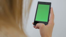 Woman using smartphone with green screen. Woman using vertical smartphone with green screen. Close up shot of woman`s hands with mobile Close up shot of woman`s stock footage