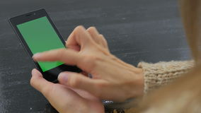 Woman using smartphone with green screen. Woman using vertical smartphone with green screen. Close up shot of woman`s hands with mobile Close up shot of woman`s stock video footage