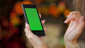 Woman using smartphone with green screen. Woman using vertical smartphone with green screen. Close up shot of woman`s hands with mobile. Elegant abstract stock video