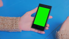Woman using smartphone with green screen. Woman using vertical smartphone with green screen. Close up shot of woman`s hands with mobile. Technology, chroma and stock footage
