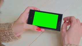 Woman using smartphone with green screen. Woman using horizontal black smartphone with green screen. Close up shot of woman`s hands with mobile. Technology stock footage