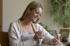 Woman using a smartphone in her home Royalty Free Stock Image