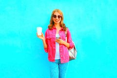 Woman using smartphone holds coffee cup Royalty Free Stock Image