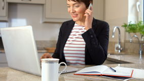Woman using smartphone and laptop. In the kitchen stock footage