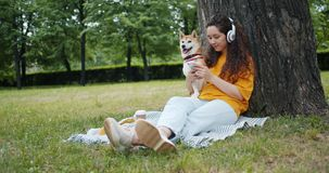 Woman using smartphone listening to music in headphones in green park with dog. Beautiful young woman is using smartphone and listening to music in wireless stock video