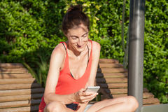 Woman using smartphone on lounge deck chair Royalty Free Stock Photos