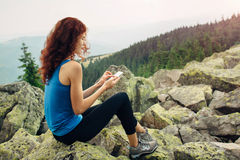 Woman using smartphone in the mountains Stock Photo