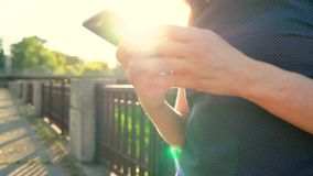 Woman using a smartphone outdoors at sunset close-up stock footage