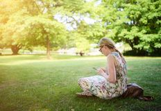Woman using smartphone in public park Stock Images