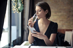 Woman using smartphone at a restaurant Stock Images