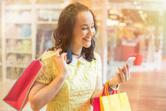 Woman using smartphone while shopping Royalty Free Stock Images