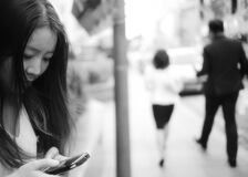 Woman Using Smartphone at Sidewalk Near Man and Woman Walking Away from Her Royalty Free Stock Images