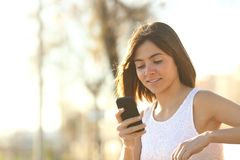 Woman using a smartphone sitting on a bench stock photo