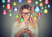 Woman using smartphone social media application icons flying out of screen Stock Photos